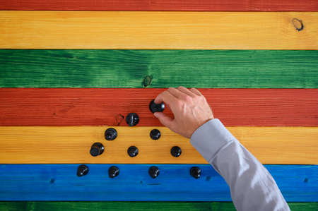 Top view of businessman hand making a pyramids shape of black chess figures over a colorful wooden background. Imagens - 128872952