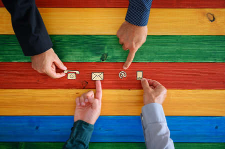 Four male hands placing paper cut contact and communication icons in a row on a colorful background of wooden boards. Top view.