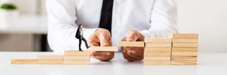 Wide view conceptual image of businessman making stairway of wooden pegs for another entrepreneur to walk upwards.