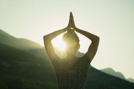 View from behind of a young woman making yoga asana with the morning sun shining through a gap between her arm and head.