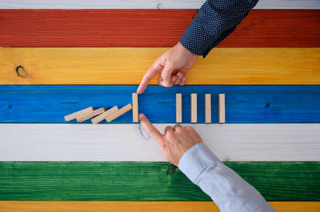 Two male hands working together to stop dominos from collapsing in a conceptual image. Over colorful background of wooden planks. Reklamní fotografie