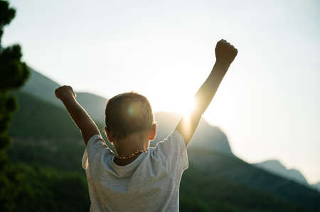 Vista da dietro di un bambino con le braccia alzate in aria che accoglie il sorgere del sole mattutino.