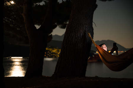 Young woman lying in a hammock browsing her mobile phone by the evening sea with moonlight reflecting in the water.