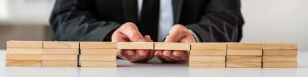 Wide view image of businessman making a bridge or connection between two stacks of wooden pegs. Banco de Imagens