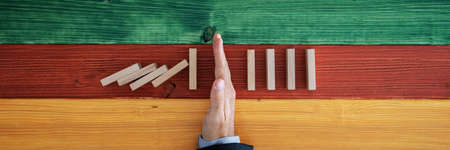 Wide view image of businessman hand stopping dominos from collapsing in a conceptual image. Over colorful background of wooden boards. 스톡 콘텐츠 - 130111617