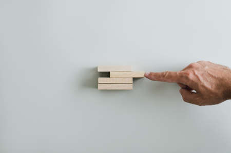 Male hand pushing wooden peg to complete a solid and stable stack of them. Over grey background with copy space.