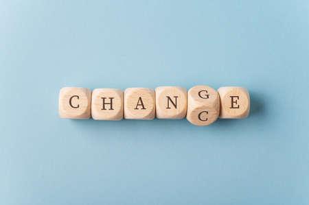 Word Change pisany drewnianymi kostkami z kostką niosącą literę G obracającą się, aby przeliterować słowo Chance. Zdjęcie Seryjne