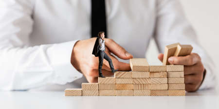 Businessman making a staircase of wooden pegs for his partner to walk upwards in a conceptual image of business partnership and support.