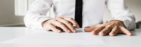 Wide view image of business manager sitting at his office desk reviewing a contract or document before signing it.