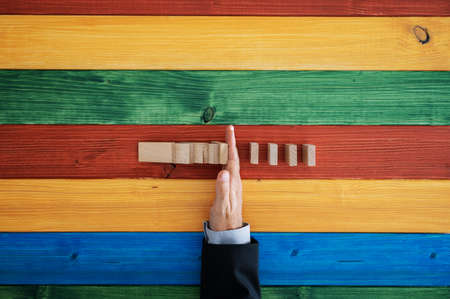 Top view of male hand stopping domino effect over colorful wooden background. Stok Fotoğraf