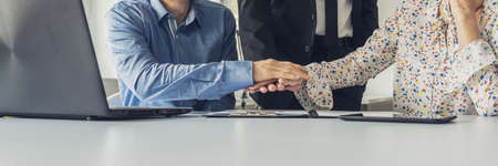 Wide view image of three business people stacking their hands above an office desk in successful collaboration.