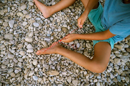 Top view of a toddler making string bracelet sitting on a pebble beach.