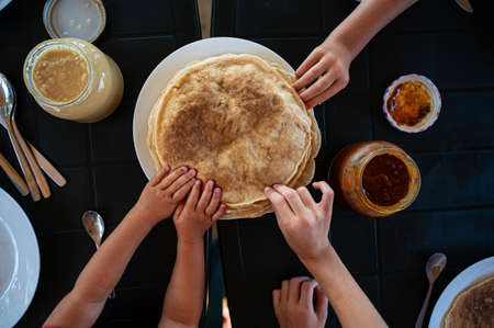 Top view of kids reaching for crepes at a breakfast table. Фото со стока