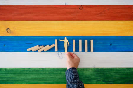 Top view of male hand placing paper cut silhouette of a man to intervene and prevent dominos from collapsing. Over colorful background of wooden boards. Фото со стока