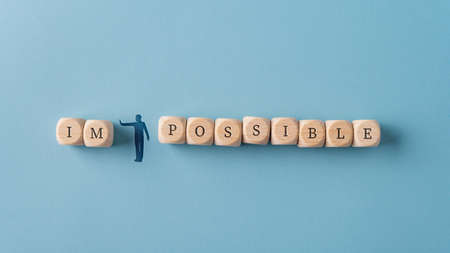 Wide view image of a silhouetted man figure pushing away letters IM from the word Impossible spelled on wooden dices. Over blue background.