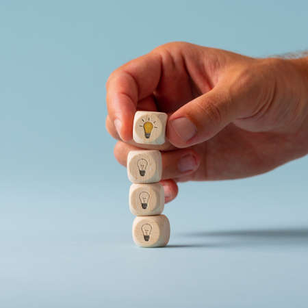 Male hand stacking wooden dices with light bulbs on them with the top one glowing yellow in a conceptual image. Over blue background. Фото со стока