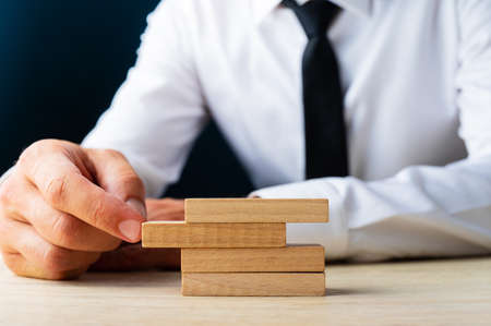 Businessman sitting at his desk pushing a peg in to a stack of them in a conceptual image of business stability.