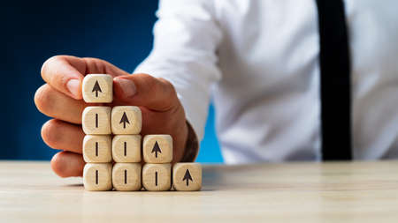 Businessman assembling wooden dices in a stairway like structure with arrows pointing upwards on the dices.