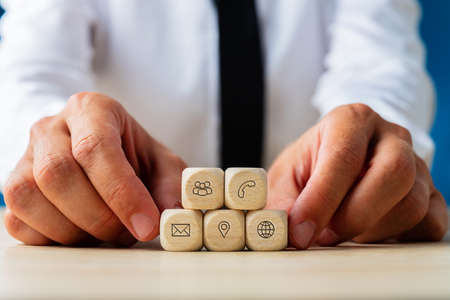 Hands of a businessman holding wooden dices with contact and communication icons of customer service on them.