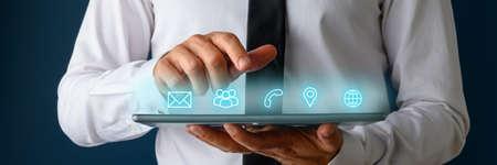 Vista frontal del empresario mediante tableta digital con iconos de contacto, comunicación y ubicación que brillan en una interfaz sobre el dispositivo. Foto de archivo