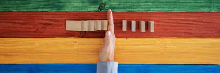 Top view of male hand intervening to stop dominos from falling in a conceptual image. Over colorful background of wooden planks Standard-Bild
