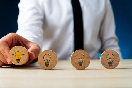 Four wooden circles with light bulb symbols on them in a row with businessman picking up the one with a glowing bulb.