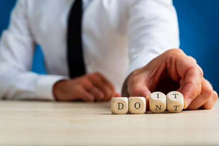 Word Dont spelled on wooden dices with businessman turning the last two dices to spell Do It sign.