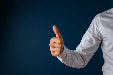 Businessman making a thumbs up gesture over a navy blue background. Фото со стока