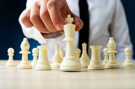 Front view of businessman sitting at his desk positioning white chess figure of king in front of the other figures in a conceptual image. Over navy blue background.