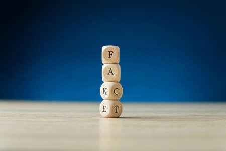 Gestapelde houten kubussen met een nep-bord met de onderste twee draaien om het woord feit te spellen. Over marineblauwe achtergrond.