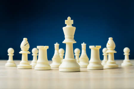 White chess pieces with the king as the leader placed on wooden desk in a conceptual image. Over blue background.