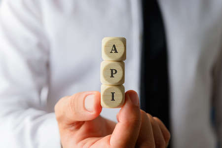 Businessman holding three dices with the API sign in a conceptual image.