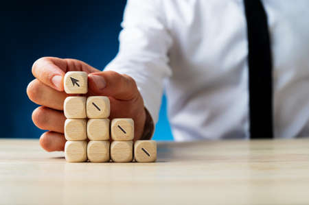 Businessman making a stack of wooden dices assembling an arrow shooting upwards in a conceptual image. Over navy blue background. Stock Photo