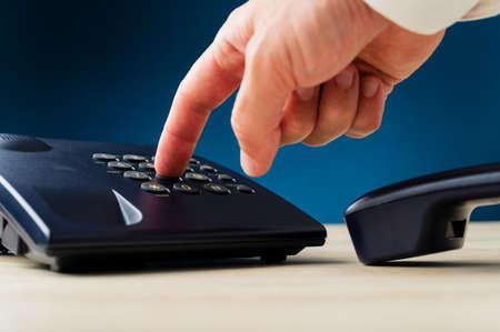Closeup of male finger pressing a button on landline telephone keypad on a desk. Over dark blue background. Stock fotó