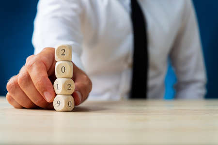 Businessman holding a stack of wooden dices carrying a 2019 sign turning in to 202. Over navy blue background. Stok Fotoğraf