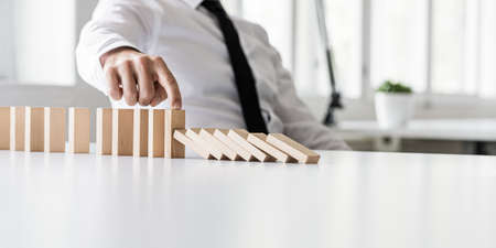 Business crisis manager preventing wooden dominos to collapse in a conceptual image.