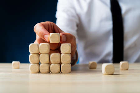 Businessman placing the last dice in a stacked structure in a conceptual image of new business. Over navy blue background.