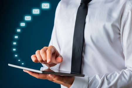 Businessman using digital tablet with shiny white envelope mail icons coming out of it. Over navy blue background. Фото со стока