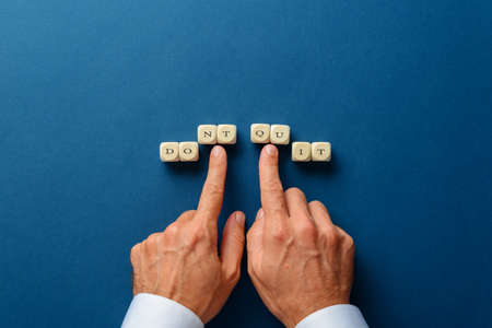 Male hand changing a  dont quit in to a do it sign spelled on wooden dices. Over dark blue background.