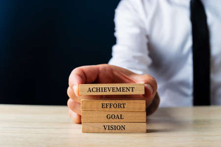 Businessman stacking wooden pegs with elementary words for business success - Vision, Goal, Effort and Achievement. Over blue background.