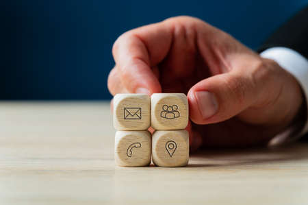 Customer service concept with businessman stacking wooden dices with contact information icons on them.