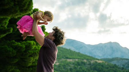 Happy young father playing with his toddler daughter wearing bright pink skirt lifting her high up in the air. Фото со стока