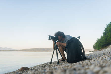 Male photographer kneeling down on pebble beach to take a picture with his dslr camera on tripod. With camera bag next to him.