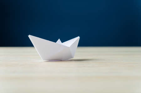 Paper made origami boat on a desk over navy blue background. Reklamní fotografie