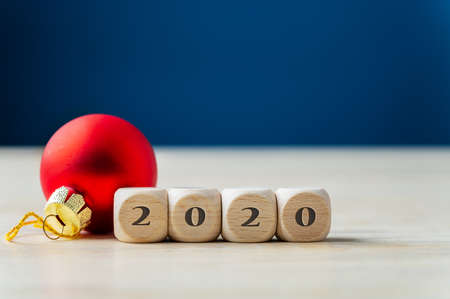 Red holiday bauble next to wooden dices with 2020 sing. Over navy blue background.