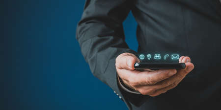 Businessman holding mobile phone with contact and communication icons glowing above it in a conceptual image. Over navy blue background.