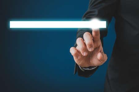Uomo d'affari che tocca una barra di ricerca bianca incandescente sull'interfaccia virtuale in un'immagine concettuale. Su sfondo blu scuro.