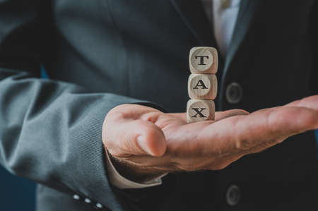 Businessman holding stacked wooden dices spelling Tax in his palm.