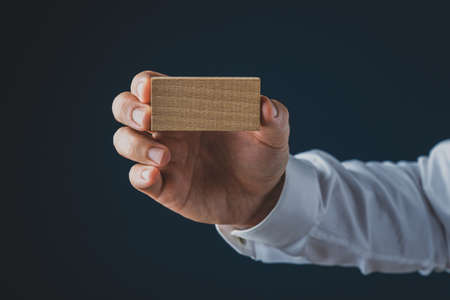 Hand of a businessman holding blank wooden peg resembling business card showing it to the camera. Over navy blue background.