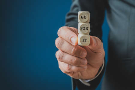 Businessman holding stacked wooden dices with Go for it sign on them. Over navy blue background with copy space. Фото со стока